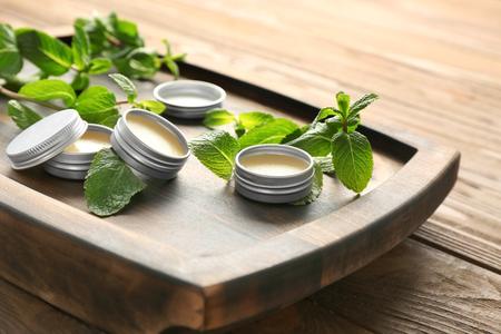 Foto de Containers with lemon balm salve and leaves on table - Imagen libre de derechos