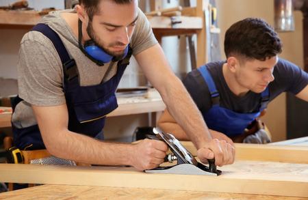 Photo pour Young carpenters working in shop - image libre de droit