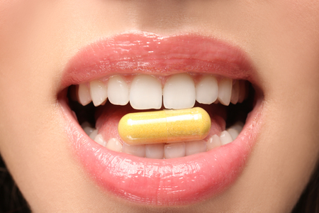 Foto de Young woman taking pill, closeup. Weight loss concept - Imagen libre de derechos