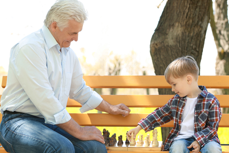 Photo pour Cute little boy with his grandfather playing chess on bench in spring park - image libre de droit