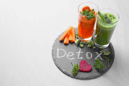 Foto per Fresh juices in glasses and ingredients on slate plate with word DETOX - Immagine Royalty Free