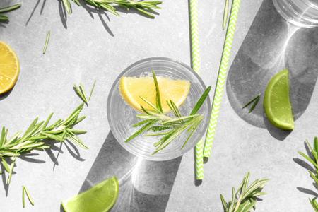 Foto de Glass of fresh lemonade with rosemary on grey background - Imagen libre de derechos