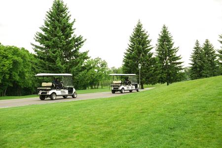 Photo pour Modern golf carts driving along the road near green course - image libre de droit