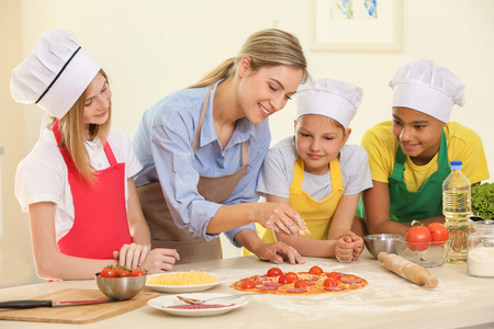Photo pour Group of children and teacher in kitchen during cooking classes - image libre de droit