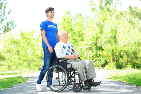 Foto de Happy senior man on wheelchair with young male volunteer outdoors - Imagen libre de derechos