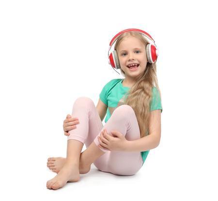 Foto de Cute funny girl with headphones listening to music on white background - Imagen libre de derechos