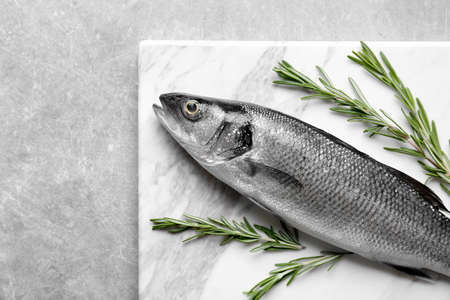 Photo pour Fresh fish with rosemary on gray background - image libre de droit