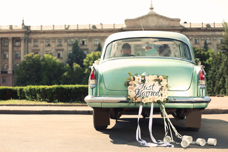 Foto de Wedding couple in car decorated with plate JUST MARRIED and cans outdoors - Imagen libre de derechos