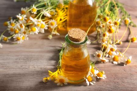 Foto de Bottle of essential oil and chamomile flowers on wooden table - Imagen libre de derechos