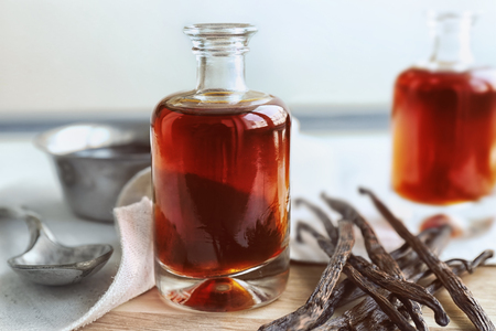 Photo for Bottle with aromatic extract and dry vanilla beans on table - Royalty Free Image