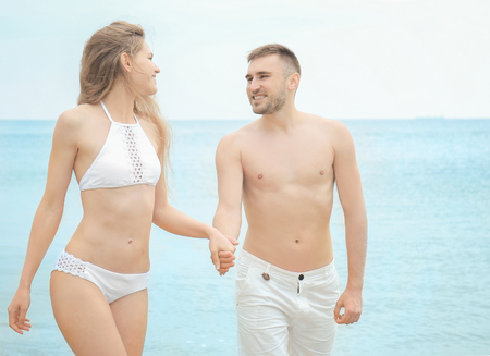 Foto de Young happy couple walking on seashore - Imagen libre de derechos