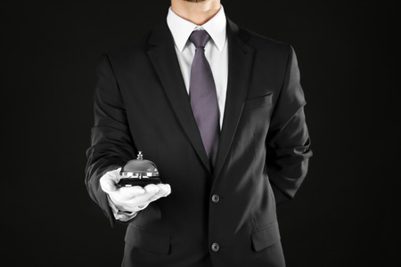 Photo pour Man holding bell on black background - image libre de droit
