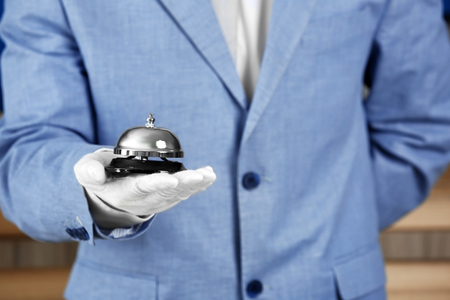Photo pour Man holding bell on blurred background, closeup - image libre de droit