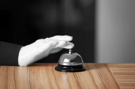 Photo pour Man ringing service bell on wooden table - image libre de droit
