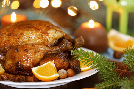 Photo for Plate with tasty whole roasted turkey on table against defocused lights - Royalty Free Image