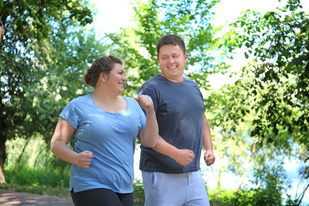 Foto per Overweight couple running in green park - Immagine Royalty Free