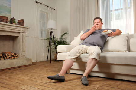 Photo pour Overweight young man eating sweets on sofa at home - image libre de droit