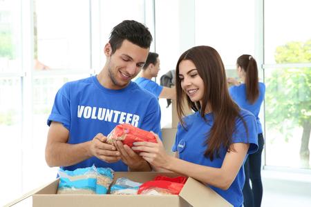 Foto de Team of teen volunteers collecting food donations in cardboard box indoors - Imagen libre de derechos