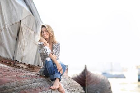 Foto de Young woman sitting on old overturned boat outdoors - Imagen libre de derechos