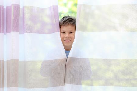 Cute little boy hiding behind curtains at home