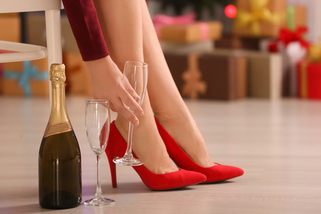 Photo pour Woman in high heel shoes holding glass for champagne at home - image libre de droit