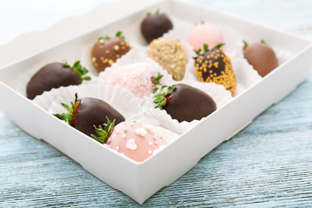Foto de Box with tasty chocolate dipped and glazed strawberries on wooden background - Imagen libre de derechos