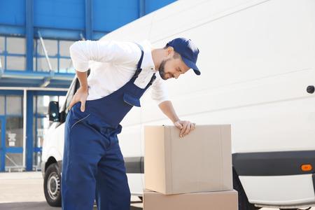 Foto de Delivery man suffering from pain after moving heavy box near car - Imagen libre de derechos