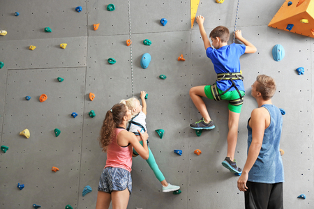 Foto de Instructors helping children climb wall in gym - Imagen libre de derechos