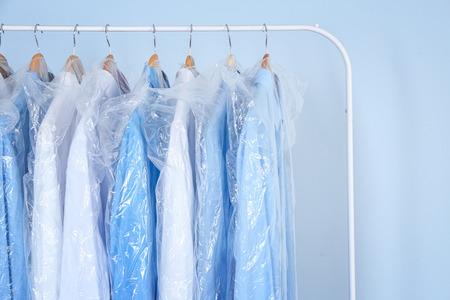 Photo pour Clean shirts hanging on rack in laundry - image libre de droit