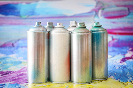 Foto de Aluminum aerosol cans with paints against blurred background - Imagen libre de derechos