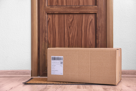 Photo for Parcel box on floor near door - Royalty Free Image
