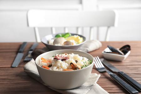 Photo pour Dish with delicious seafood risotto on wooden table - image libre de droit