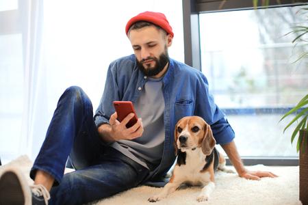 Foto de Handsome young hipster with dog at home - Imagen libre de derechos