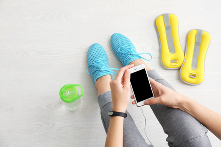 Photo for Young woman with mobile phone sitting on floor, flat lay. Ready for gym workout - Royalty Free Image