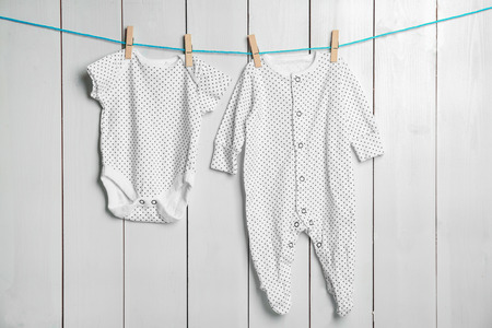 Photo pour Children's clothes on laundry line against wooden background - image libre de droit