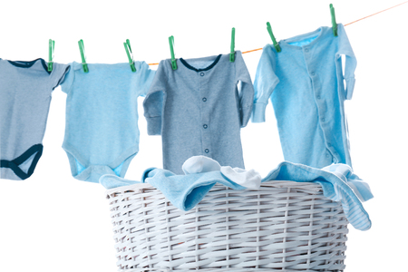 Photo for Children's clothes on washing line and laundry basket against white background - Royalty Free Image