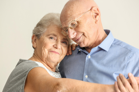 Foto per Cute elderly couple dancing against light background - Immagine Royalty Free