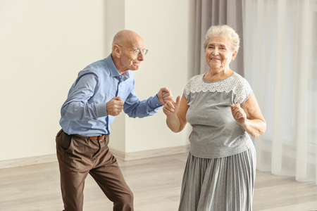 Photo pour Cute elderly couple dancing at home - image libre de droit
