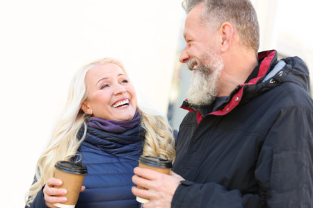 Foto per Happy mature couple drinking coffee outdoors on autumn day - Immagine Royalty Free