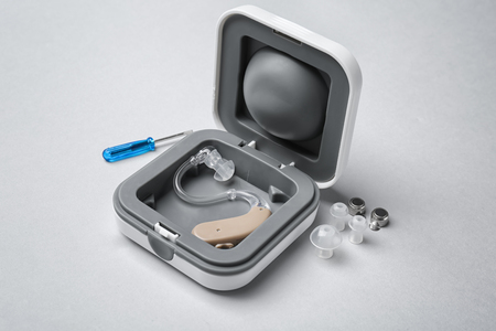 Photo pour Hearing aid with accessories on light background - image libre de droit