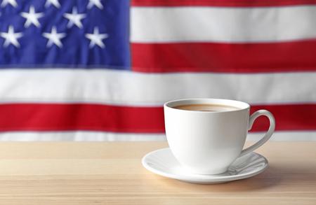 Foto de Cup of hot coffee on table against flag of the USA - Imagen libre de derechos
