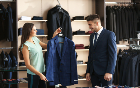 Photo for Female shop assistant helping man to choose suit in store - Royalty Free Image