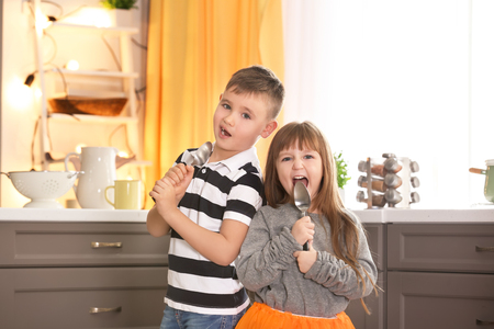 Photo for Cute little children using spoons as microphone in kitchen - Royalty Free Image