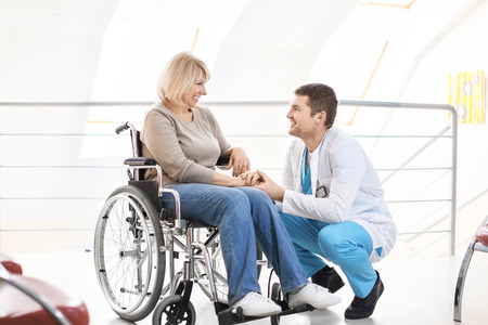 Photo pour Male doctor taking care of mature woman in wheelchair indoors - image libre de droit