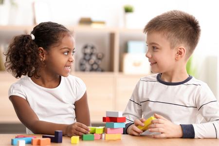 Foto de Little kids playing indoors. Child adoption - Imagen libre de derechos