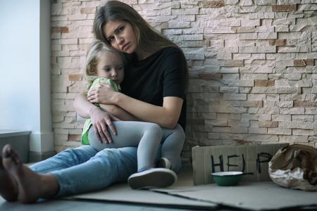 Foto de Homeless poor woman and her little daughter sitting near brick wall and asking for help - Imagen libre de derechos
