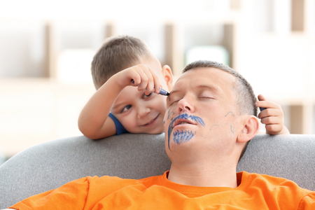 Foto de Little boy painting his father's face while he sleeping. April fool's day prank - Imagen libre de derechos