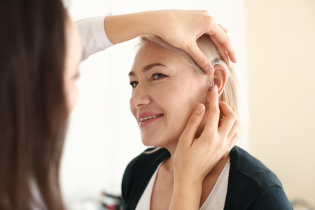 Photo for Otolaryngologist putting hearing aid in woman's ear on light background - Royalty Free Image