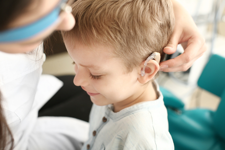 Photo for Otolaryngologist putting hearing aid in little boy's ear indoors - Royalty Free Image