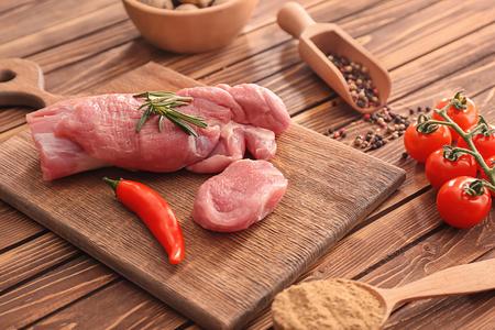 Photo pour Board with raw pork tenderloin on kitchen table. Fresh meat products - image libre de droit